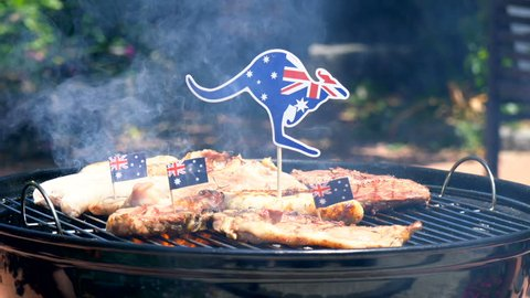 Iconic Australian BBQ close up of man cooking chops, sausgaes and steak, outdoors in garden setting.