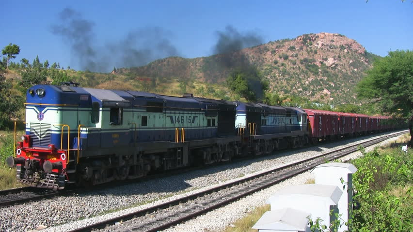 A Freight Goods Train Is Passing By A Rural Remote Station