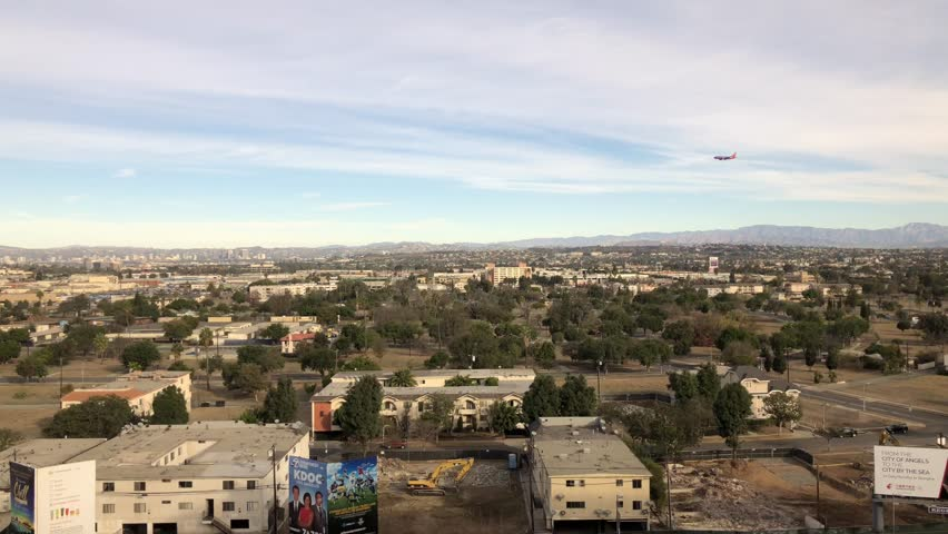 LOS ANGELES, CA, USA - SEP 12, 2017: LA Skylines by the airport with Southwest Airplane flying over descending towards LAX Airport. | Shutterstock HD Video #33876727