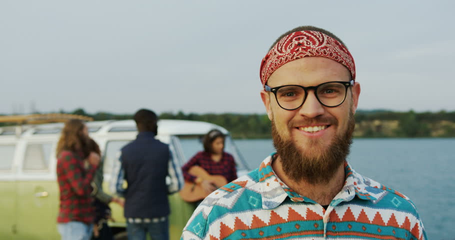 Young male hipster in glasses standing in front of the camera. Group of the mixed races friends on the background near a green van and a lake. Outside. Portrait shot. Close up