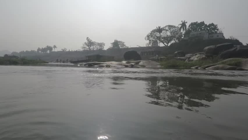 Crossing river in Hampi, India. Smooth shot passes Shiva lingams in water, islands, grass, and men bathing an elephant. 2X slow motion