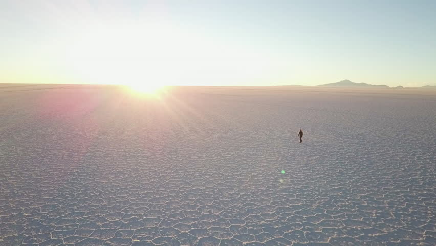 Long shadow of person walking on the Salar de Uyuni in Bolivia at sunset