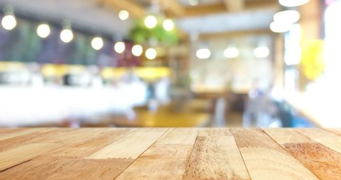 Wood table top on blurred restaurant interior background with blinking light bokeh - can be used for display or montage your products (food)