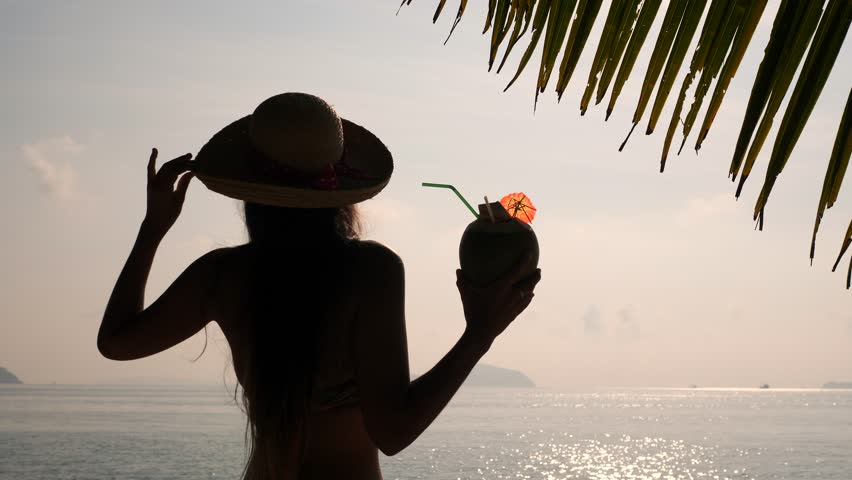 Silhouette of Young Tourist Girl Drinking Fresh Thai Coconut Cocktail at Tropical Beach. 4K, Slowmotion. Phuket, Thailand.
