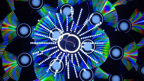 Compact disks shimmer all the colors of the rainbow when you direct a beam of light.  Disks is rotation and reflection a luminous ring with rays. Closeup