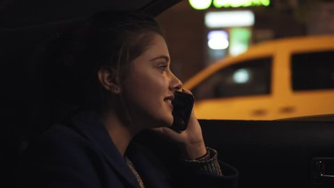Happy smiling girl riding in a taxi at night sitting on the backseat and speaking on the smartphone. Happy woman in taxi. Night live. Slowmotion shot