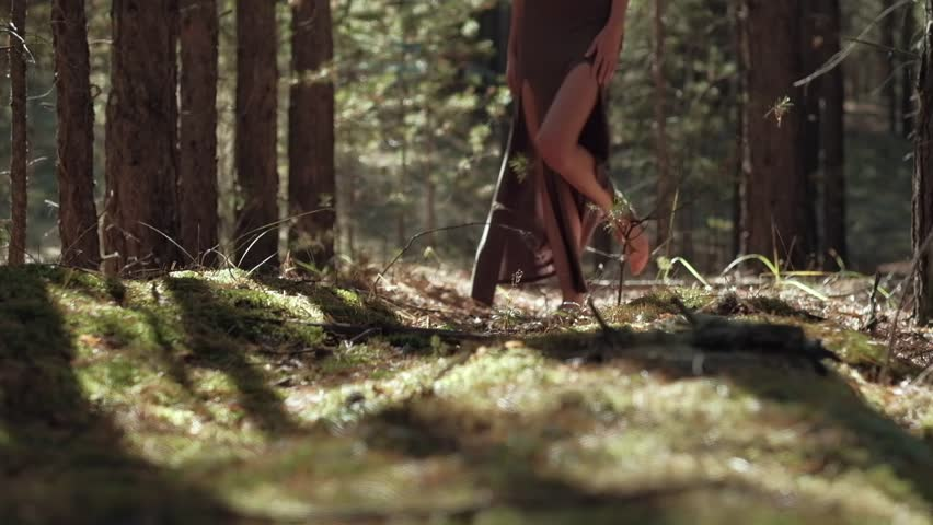A young girl's bare feet go on a forest of soft moss, long dress, the slender legs of the models walking on camera #33927547