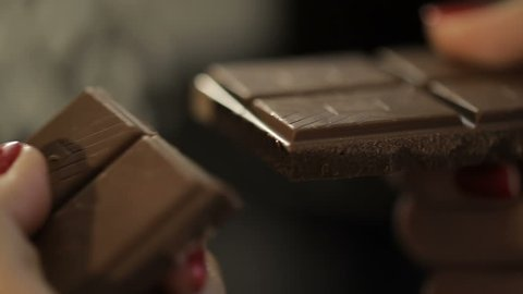 Woman breaks chocolate bar. Slow motion