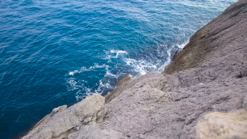 Calm sea waves gently washing the rough cliff, amazing nature and relaxation