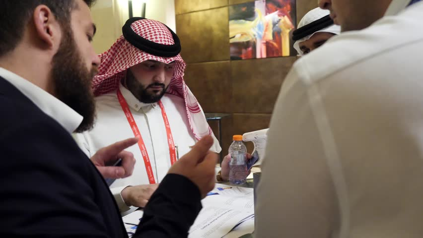 DUBAI, UAE - MAY 12, 2017: Dubai World Trade Centre, group of multi ethnic business people dealing a contract and hand shaking. Successful Arabic business people shaking hands over a deal