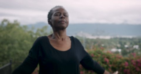 Active baby boomer African American woman in 60s exercising yoga sun salutation poses outdoors with great view