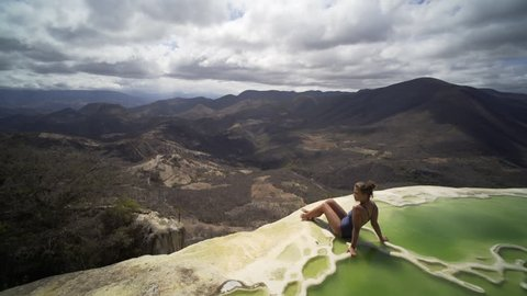 young women sitting on the brink of mineral pool, crane shot open beautiful view, Mexico Hierve el Agua