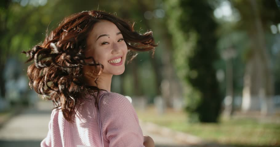 close-up of beautiful Asian girl in Sunny day in the Park,turn on the camera with a smile slow motion