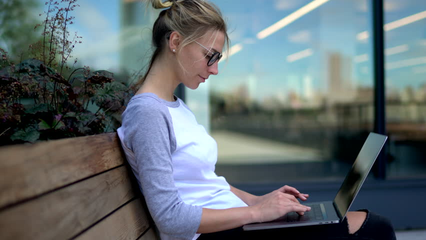 Cheerful hipster girl in eyewear messaging with friend in online chat and sharing posts in social networks on modern laptop computer sitting outdoors on territory of campus | Shutterstock HD Video #33980482