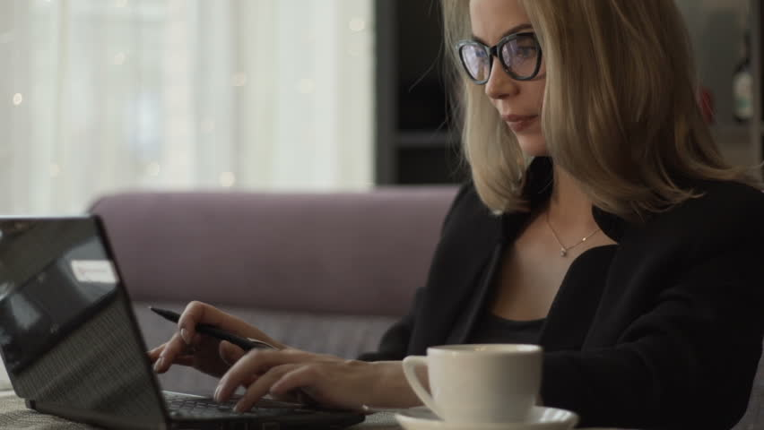 Young woman in glasses typing on keyboard notebook sitting at couch in cafe with coffee cup. Beautiful woman working on laptop during business lunch in modern cafe | Shutterstock HD Video #33985762