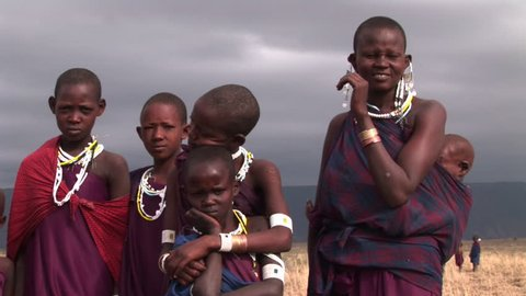 African family, mother and children pose in a village. Stormy sky.