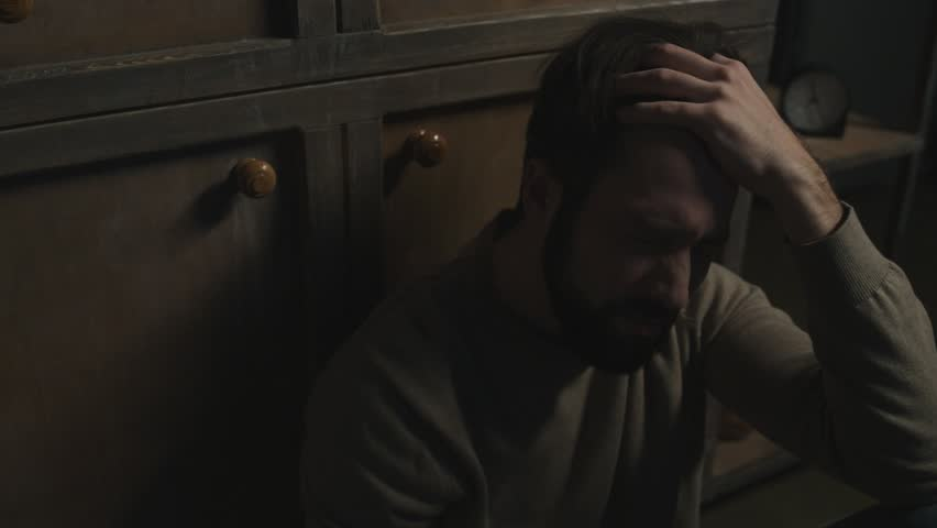 In despair. Close up of young bearded man sitting on the floor while drinking alcohol and expressing sadness | Shutterstock HD Video #34017127