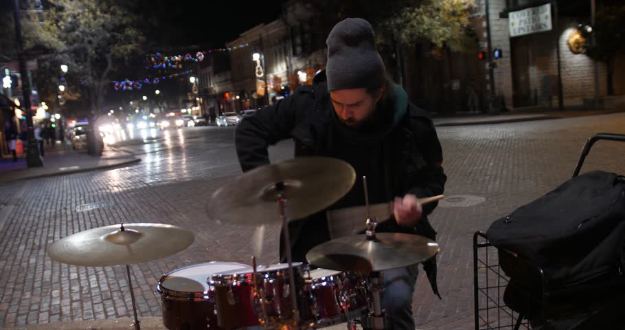 AUSTIN, TX - Circa December, 2017 - A street performer plays the drums for passing tourists on E 6th Street in downtown Austin, Texas at night. With audio.