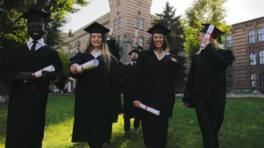 Multi-ethnical male and female graduates in black traditional gowns and caps walking cheerfully and talking with their diplomas in hands from the University building. Outdoors