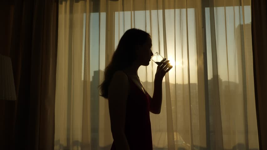 Young woman take one gulp of water, silhouetted view against living room window, sunrise outside. Half length shot of long haired lady, enjoying good morning time, healthy lifestyle concept