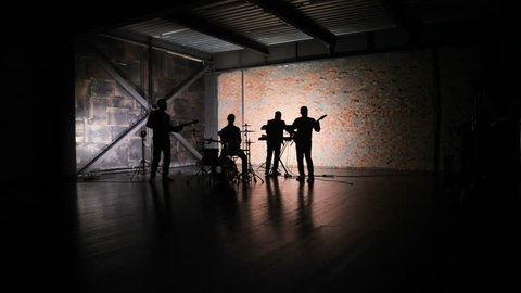silhouette of Concert rock band performing on stage with singer performer, guitar, drummer, keyboardist. Music video punk, heavy metal or rock group.