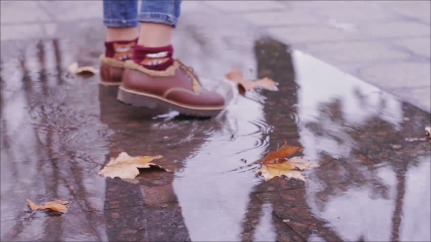 Brown leather boots walk in a puddle with fallen leaves. Close up of cute woman shoes in autumn streets background.  | Shutterstock HD Video #34067047