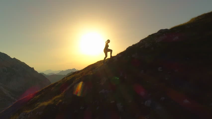 AERIAL SILHOUETTE: Flying over young woman hiker as she climbs up sloping terrain on her way to summit. Woman trying to reach mountain peak before sundown. Lady climbing uphill in beautiful scenery.