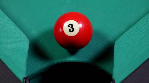 Close up of a billiard ball with number 3 falling into the billiard table hole