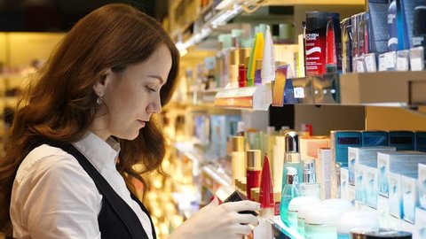 ISTANBUL - NOVEMBER 02, 2017: Pensive young adult woman (model released) choosing facial cream at store, take one from shelf. Lady at face treatment and skin care section of duty free shop