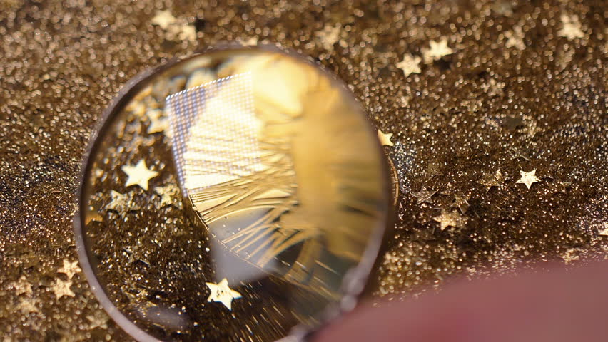 macro person hand with loupe over golden coin created as most popular digital currency in world