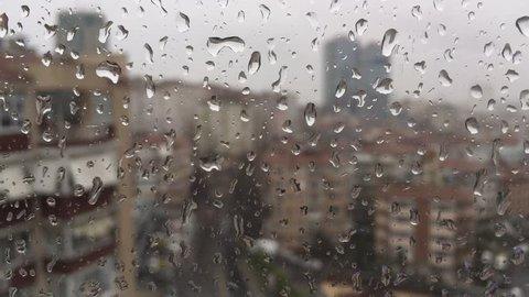 rain drops on windowpane against buildings