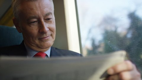 Business man on a train checking share prices in a paper, in slow motion