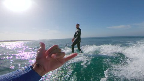 SLOW MOTION LENS FLARE POV Stoked cameraman giving shaka sign to young surfer successfully riding a wave. Surfboarder riding a wave and jumping into water as man behind camera congratulates his friend