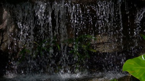 Water fall close up slow motion on dark black background. Beautiful waterfall on hills flowing on stone on nature. It fresh scenic and splash stream wet on summer on show perfect garden environment