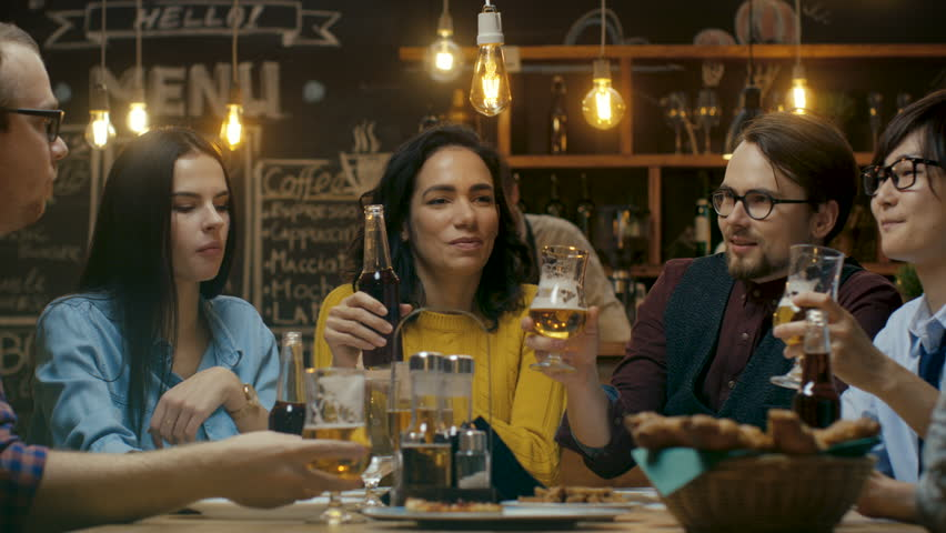 Diverse Group of Friends Celebrate with a Toast and Clink Raised Glasses with Various Drinks in Celebration. Beautiful Young People Have Fun in the Stylish Bar/ Restaurant.  | Shutterstock HD Video #34161247