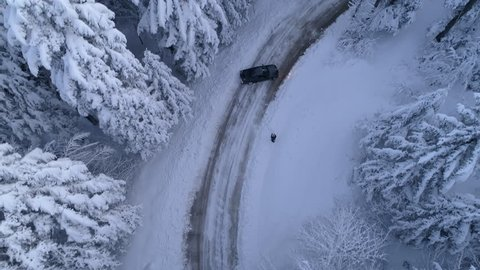 Aerial - Top down view of one man filming black car drifting on snowy road in forest (slow motion)