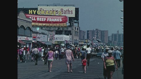 NEW YORK, 1971, Boardwalk crowded with people, Frankfurter and Bathhouse sign at Coney Island, Brooklyn