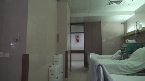 Caucasian female medical technician walks through the hall into patient room and prepares hemodialysis machine before patient treatment,steady cam, tracking, close up,concept medical equipment, indoor