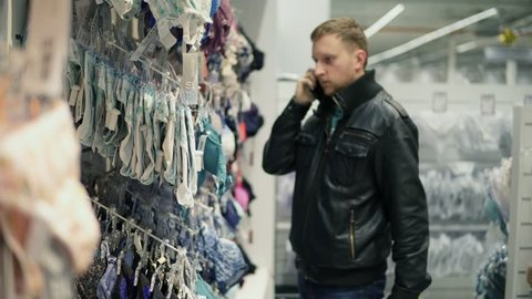 Young man is trying to choose a bra in lingerie store for his girlfriend or wife while talking on the phone and asking about size and color