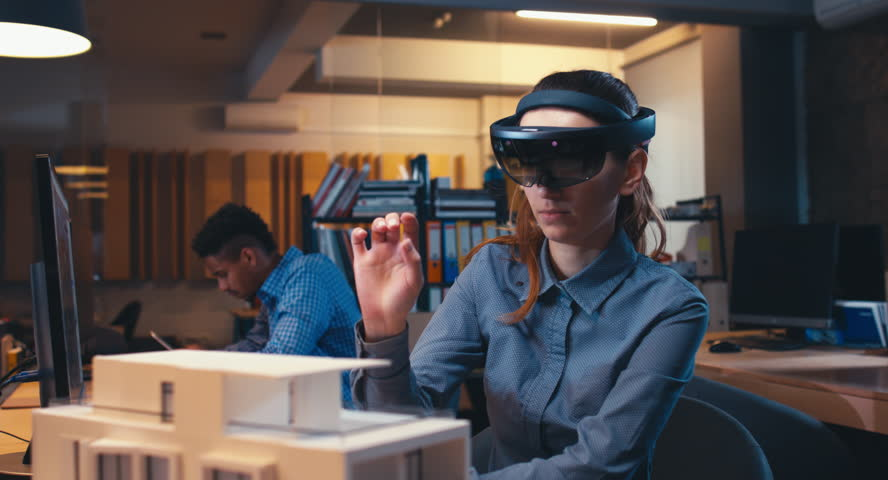Caucasian female professional architect using augmented reality AR hololens headset to work on a house project. 4K UHD RAW edited footage