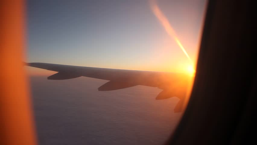 video footage of a flying airplane over the clouds in the evening