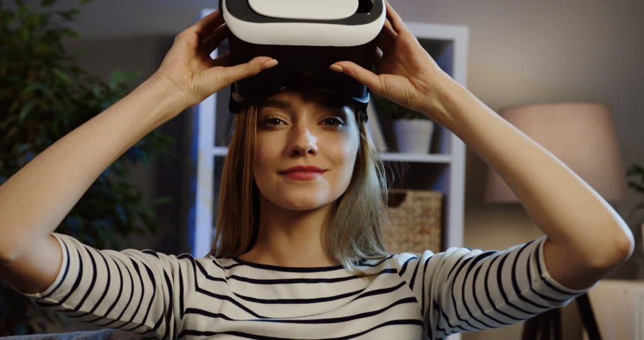 Beautiful blonde woman taking on the VR glasses and having a VR headset, moving her hands in the air and making scary gesture on the couch at home in the evening. Close up. Portrait. Indoor