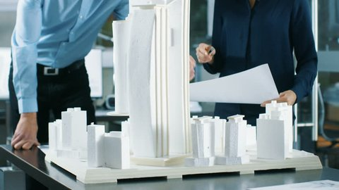 In the Architectural Bureau TwoProfessional Engineers Work on a Model of a City District. Urban Planners Work on a Functional Building Model. Shot on RED EPIC-W 8K Helium Cinema Camera.
