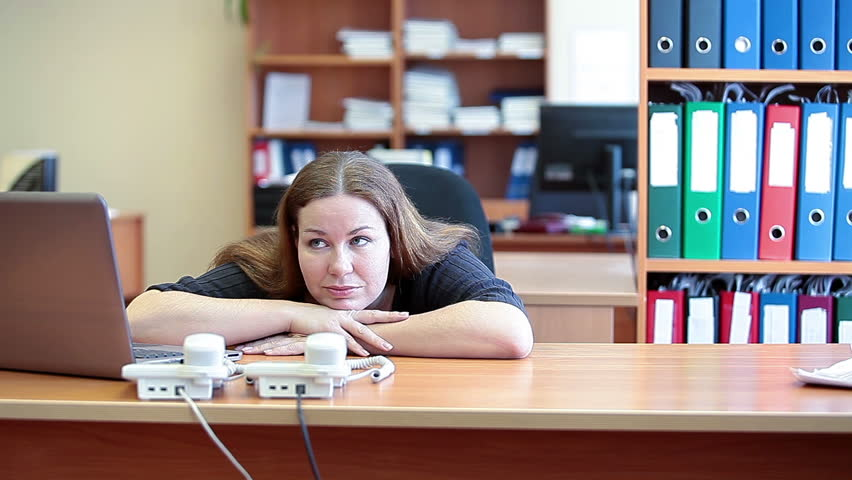 Bored young Caucasian businesswoman sitting alongside a laptop and lazing