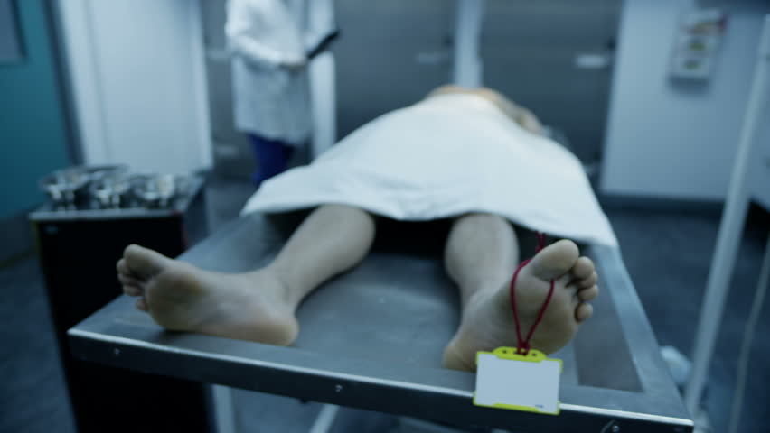 The lifeless naked body of a young mixed race male is laid out on the autopsy table, ready for the medical examiner to begin his work. In slow motion.