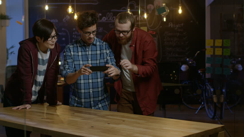 Great Concept For Augmented Reality Mock-up. Three Young Developers Look at Augmented Reality Through Smarthpone. They're Working on the New Virtual Reality Game. Shot on RED EPIC-W 8K Helium Camera. | Shutterstock HD Video #34327807