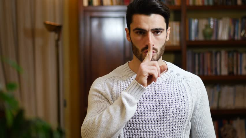 Handsome young man doing Hush sign with finger on lips, looking at camera. On location, at home in living-room
