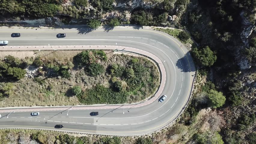 Aerial 4k shot of Country road.  Sport Car driving along the road surrounded by trees and forest. Hairpin turn in the forest. Aerial view of a curved winding road with cars passing