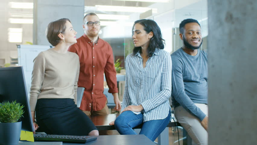 Posing Shot of a Diverse Group of Talented Young Business People Sitting on a Desk in the Modern Office Environment. Real People Sincerely Smiling on Camera. Shot on RED EPIC-W 8K Helium Cinema Camera