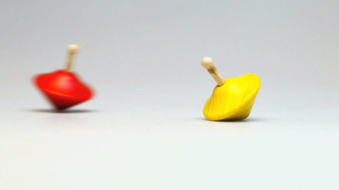 Cinemagraph - Two wooden and colorful spinning tops , red one in perpetual motion